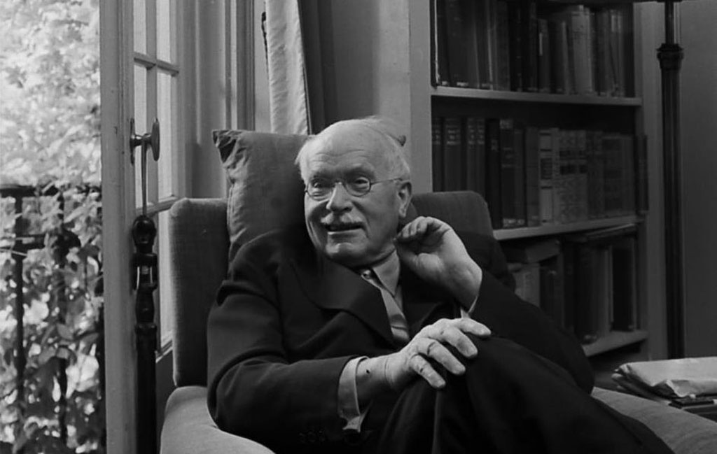 Swiss psychiatrist Dr. Carl Jung relaxing in an easy chair in his library at home in Knusnacht, Switzerland, 1949